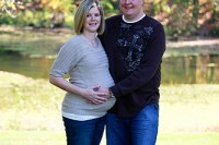 pregnant woman and man posing in park in front of lake